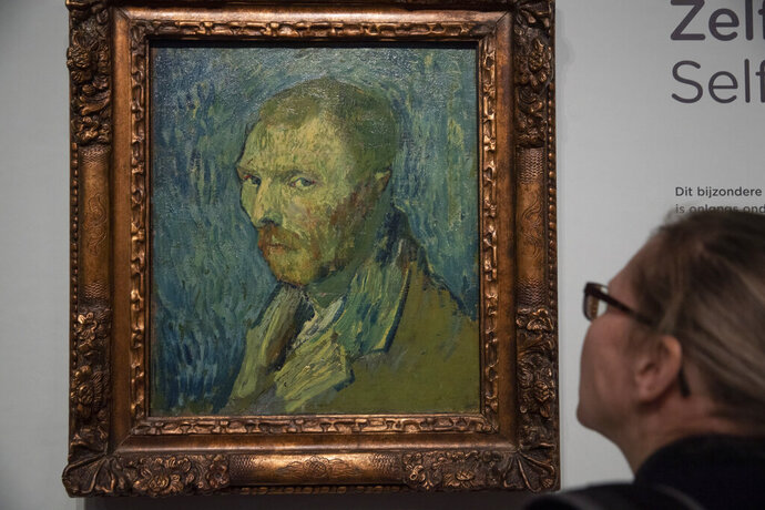 A journalist takes a closer look at the previously contested painting by Dutch master Vincent van Gogh, a 1889 self-portrait, of which the authenticity was confirmed during a press conference in Amsterdam, Netherlands, Monday, Jan. 20, 2020. The painting, which belongs to the National Museum in Norway, was painted at the Saint-Paul de Mausole psychiatric institution in Saint-Remy de Provence, France. (AP Photo/Peter Dejong)
