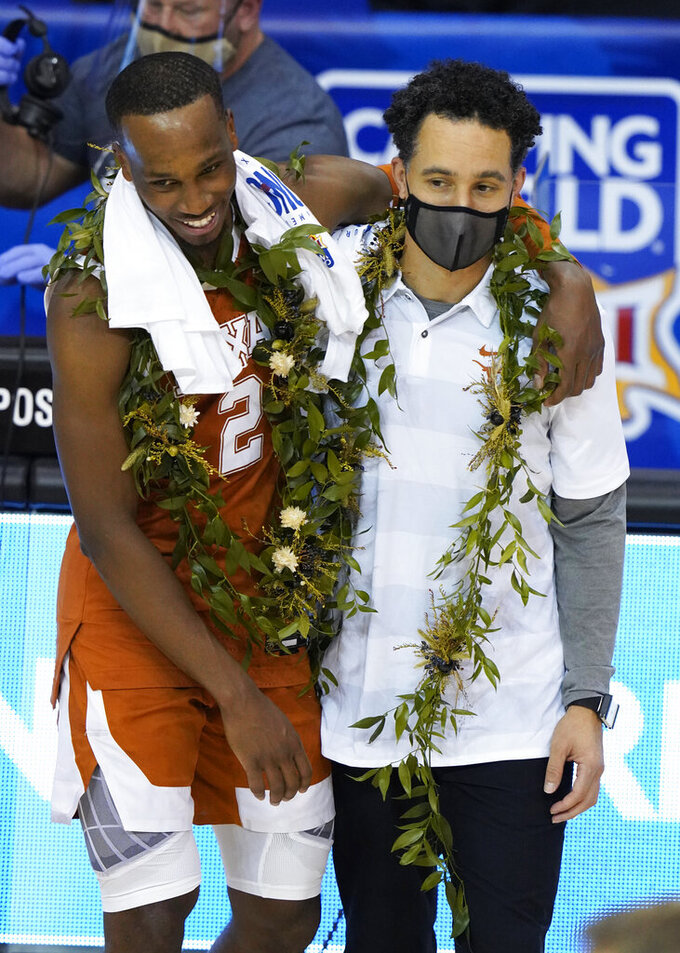 Texas guard Matt Coleman III (2) hugs head coach Shaka Smart after their team beat North Carolina 69-67 to win the NCAA college basketball game championship for the Maui Invitational, Wednesday, Dec. 2, 2020, in Asheville, N.C. Coleman was the MVP with the winning basket and high score of 22 points.(AP Photo/Kathy Kmonicek)