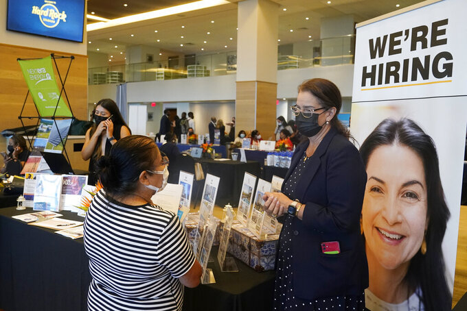 Marriott human resources recruiter Mariela Cuevas, left, talks to Lisbet Oliveros, during a job fair at Hard Rock Stadium, Friday, Sept. 3, 2021, in Miami Gardens, Fla.  The number of Americans seeking unemployment benefits fell sharply last week to 310,000, a pandemic low and a sign that the surge in COVID-19 cases caused by the delta variant has yet to lead to widespread layoffs. (AP Photo/Marta Lavandier)