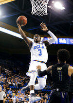 UCLA guard Aaron Holiday, left, goes up for a basket against Washington guard David Crisp during the second half of an NCAA college basketball game in Los Angeles, Sunday, Dec. 31, 2017. UCLA won 74-53. (AP Photo/Ringo H.W. Chiu)p