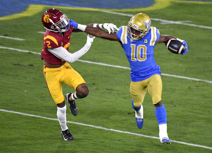 UCLA running back Demetric Felton, right, runs for a first down as Southern California's Olaijah Griffin defends during the first half of an NCAA college football game Saturday, Dec. 12, 2020, in Pasadena, Calif. (Keith Birmingham/The Orange County Register via AP)