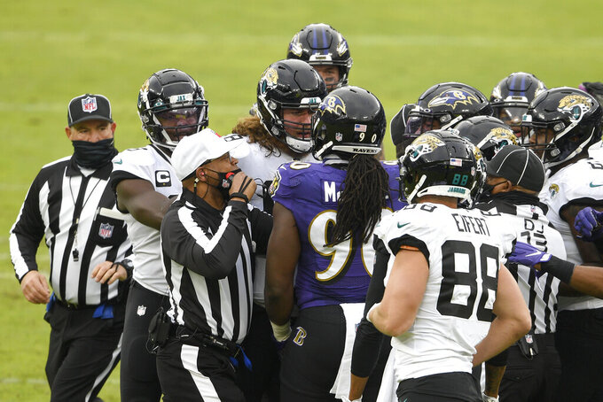 NFL referee Ron Torbert (62) tries to break up an argument between Jacksonville Jaguars guard Andrew Norwell, fourth from left, and Baltimore Ravens linebacker Pernell McPhee (90) during the first half of an NFL football game, Sunday, Dec. 20, 2020, in Baltimore. (AP Photo/Nick Wass)