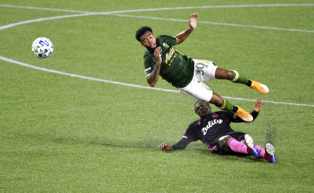 Portland Timbers midfielder Eryk Williamson, left, is upended by Seattle Sounders defender Nouhou Tolo during the first half of an MLS soccer match in Portland, Ore., Wednesday, Sept. 23, 2020. (AP Photo/Steve Dykes)