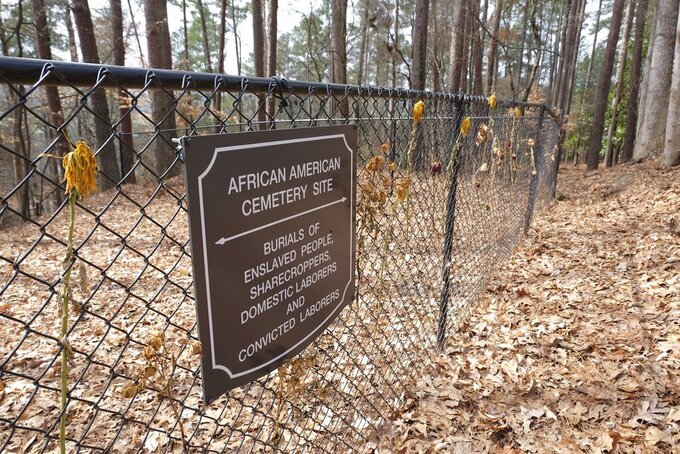 Flowers adorn a fence marking an African American cemetery site at Woodland Cemetery in Clemson, South Carolina on Sunday, Feb.  28, 2021.   Students at Clemson University who found an unkempt graveyard on campus last year sparked the discovery of more than 600 unmarked graves most likely belonging to enslaved Black people, sharecroppers and convicted laborers. The revelation has Clemson working to identify the dead and properly honor them amid a national reckoning by universities about their legacies of racial injustice.  (AP Photo/Michelle Liu)