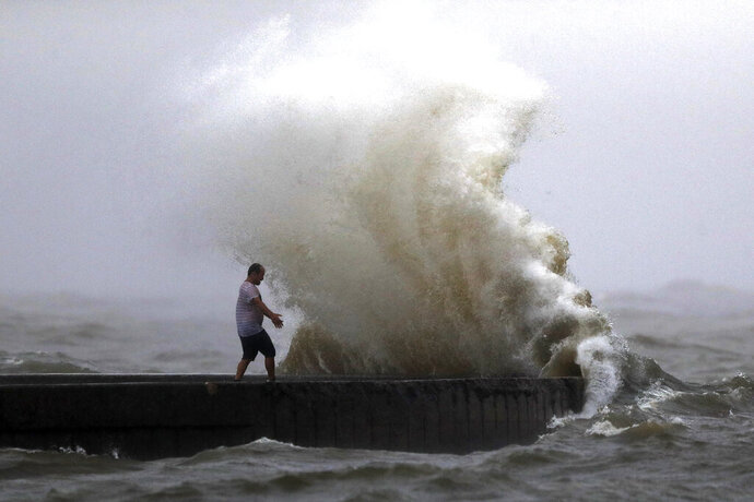 A wave crashes as a man stands on a jetty near Orleans Harbor in Lake Pontchartrain in New Orleans, Sunday, June 7, 2020, as Tropical Storm Cristobal approaches the Louisiana Coast. (AP Photo/Gerald Herbert)
