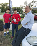 Ra Nam, right, with his sons Evan, left, and Tristan, center, wait in a parking lot outside their Colonial Heights neighborhood which was evacuated Thursday, Sept. 13, 2018, in Lawrence, Mass., due to fires and explosions triggered by a problem with a gas line that feeds homes in several communities north of Boston. (AP Photo/Phil Marcelo)