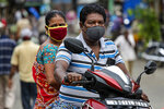 A couple wearing face masks as a precaution against the coronavirus travel on a two wheeler in Kolkata, India, Sunday, Aug. 2, 2020. India is the third hardest-hit country by the COVID-19 pandemic in the world after the United States and Brazil. (AP Photo/Bikas Das)