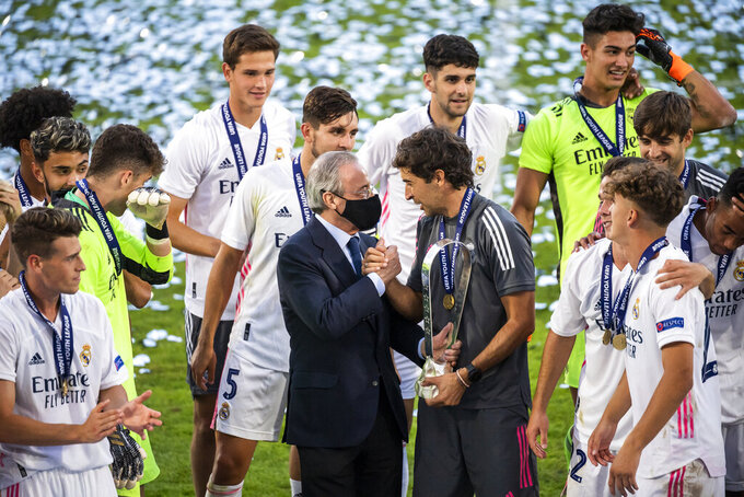 Real Madrid's team players with Real Madrid president Florentino Perez, centre left and Real Madrid's head coach Raul Gonzalez Blanco,celebrate with the trophy after winning the UEFA Youth League final soccer match between SL Benfica from Portugal and Real Madrid CF from Spain at the Colovray Sports Centre stadium in Nyon, Switzerland, Tuesday, Aug. 25, 2020. (Jean-Christophe Bott/Keystone via AP)