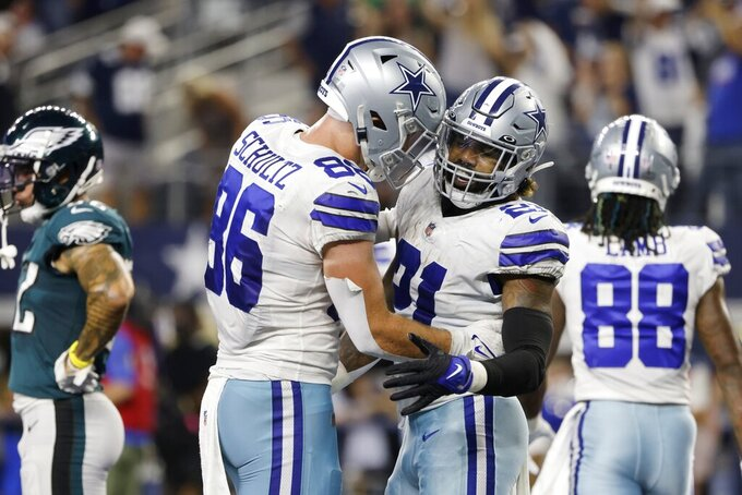 Dallas Cowboys tight end Dalton Schultz (86) and running back Ezekiel Elliott (21) celebrate a touchdown score by Elliott on a running play in the first half of an NFL football game against the Philadelphia Eagles in Arlington, Texas, Monday, Sept. 27, 2021. (AP Photo/Michael Ainsworth)