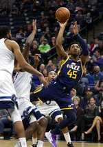 Utah Jazz guard Donovan Mitchell (45) shoots past Minnesota Timberwolves center Karl-Anthony Towns, left, forward Andrew Wiggins (22) and guard Jeff Teague (0) during the second quarter of an NBA basketball game Wednesday, Nov. 20, 2019, in Minneapolis. (AP Photo/Andy Clayton-King)