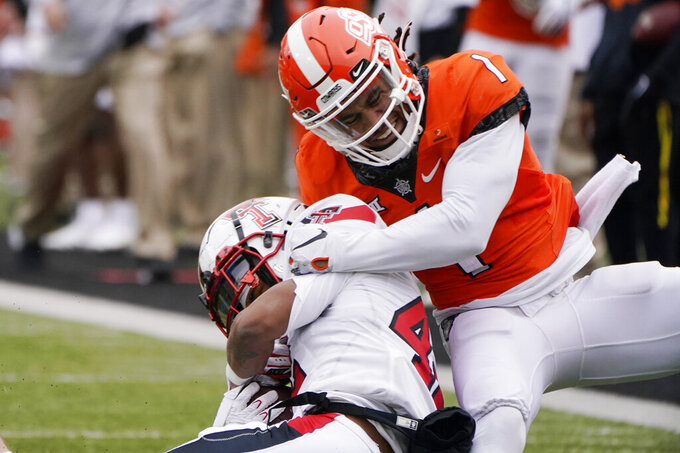 Oklahoma State linebacker Calvin Bundage, right, tackles Texas Tech running back Chux Nwabuko III, left, in the second half of an NCAA college football game in Stillwater, Okla., Saturday, Nov. 28, 2020. (AP Photo/Sue Ogrocki)