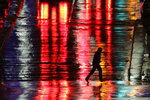 A man is silhouetted as he crosses a rain-covered street on a cold, windy night Tuesday, Nov. 26, 2019, in Kansas City, Mo. The area is forecast to have cold wet weather for the Thanksgiving holiday. (AP Photo/Charlie Riedel)