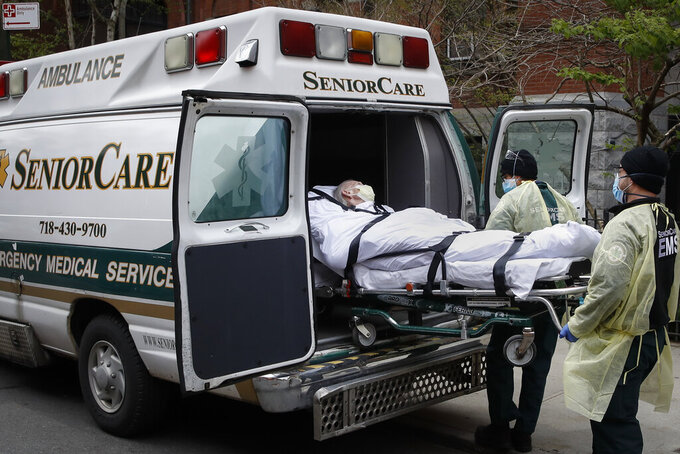 FILE - In this April 17, 2020, file photo, a patient is loaded into an ambulance by emergency medical workers outside Cobble Hill Health Center in the Brooklyn borough of New York. Deaths among Medicare patients in nursing homes soared by more than 30% last year, with two devastating surges eight months apart, a government watchdog reported Tuesday in the most complete assessment yet of the ravages of COVID-19 among its most vulnerable victims. (AP Photo/John Minchillo, File)