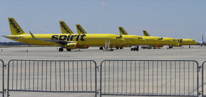 FILE - A line of Spirit Airlines jets sit on the tarmac at the Orlando International Airport Wednesday, May 20, 2020, in Orlando, Fla. Spirit Airlines is warning, Wednesday, July 29, 2020, employees that it could furlough up to 30% of its roughly 9,000 workers in October, when federal payroll-help money runs out. (AP Photo/Chris O'Meara)