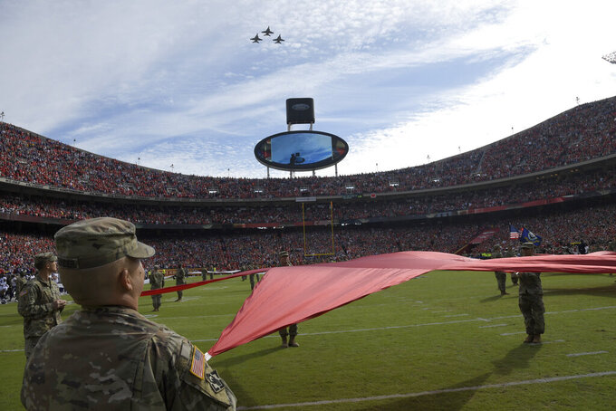 Service members hold a star as three F-18 jets fly above before the first half of an NFL football game in Kansas City, Mo., Sunday, Nov. 3, 2019. (AP Photo/Reed Hoffmann)