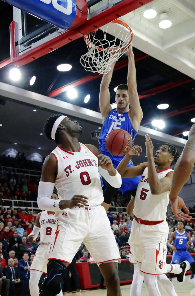 St. John's Sedee Keita (0) and Justin Simon (5) watch as Creighton's Martin Krampelj (15) dunks the ball during the first half of an NCAA college basketball game Wednesday, Jan. 16, 2019, in New York. (AP Photo/Frank Franklin II)