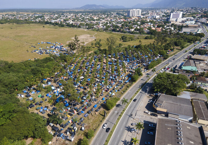 """FILE - In this May 26, 2021 file photo, tents and shacks cover land designated for a Petrobras refinery, called the """"First of May Refugee Camp,"""" which refers to the date the squatters camp sprung up amid the new coronavirus pandemic, in Itaguai, Rio de Janeiro state, Brazil. In the first quarter of 2021, Brazil saw its highest unemploymentand economic inequality in at least nine years, with the cost of living surging and tent cities and shantytowns emerging. (AP Photo/Mario Lobao, File)"""
