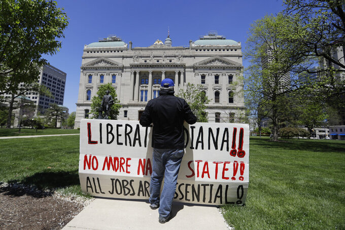 A protester holds a signs during a 'Indiana Back to Work' rally at the Statehouse, Friday, May 1, 2020, in Indianapolis. Indiana Gov. Eric Holcomb says any easing of Indiana's statewide stay-at-home order won't limit the authority of city or county officials from imposing tighter restrictions in their attempts to slow the spread of the coronavirus. (AP Photo/Darron Cummings)
