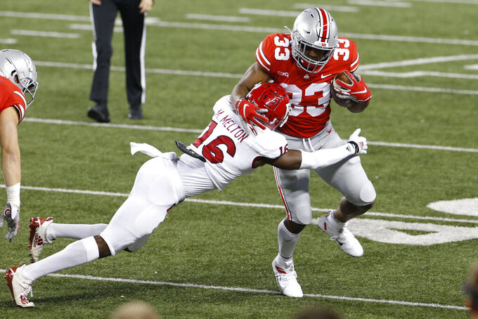 Ohio State running back Master Teague, right, cuts upfield against Rutgers defensive back Max Melton during the first half of an NCAA college football game Saturday, Nov. 7, 2020, in Columbus, Ohio. (AP Photo/Jay LaPrete)