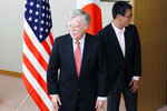 Japanese Foreign Minister Taro Kono, right, and U.S. National Security Advisor John Bolton, left, walk for their meeting in Tokyo Monday, July 22, 2019. (AP Photo/Eugene Hoshiko)