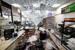 Shattered glass hangs from the doorway of a 7-Eleven store early Sunday morning, May 31, 2020 in Chicago, after a night of unrest and protests over the death of George Floyd, a black man who was in police custody in Minneapolis. Floyd died after being restrained by Minneapolis police officers on Memorial Day. (AP Photo/Charles Rex Arbogast)