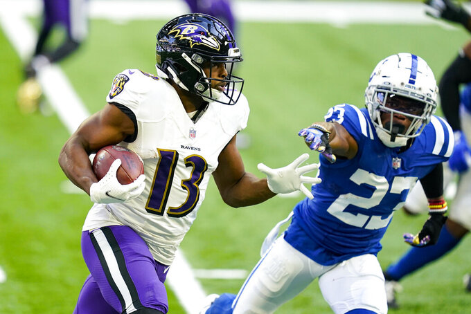 Baltimore Ravens wide receiver Devin Duvernay (13) runs around Indianapolis Colts cornerback Kenny Moore II (23) in the first half of an NFL football game in Indianapolis, Sunday, Nov. 8, 2020. (AP Photo/Darron Cummings)
