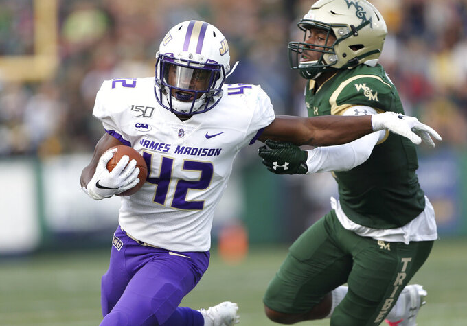 James Madison's Solomon Vanhorse (42) runs away from William & Mary's Isaiah Laster, right, during the first half of an NCAA college football game in Williamsburg, Va., on Saturday, Oct. 19, 2019.  (Daniel Sangjib Min/Richmond Times-Dispatch via AP)