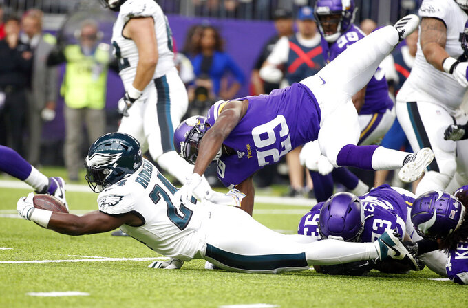 Philadelphia Eagles running back Jordan Howard (24) is tackled by Minnesota Vikings cornerback Xavier Rhodes (29) during the first half of an NFL football game, Sunday, Oct. 13, 2019, in Minneapolis. (AP Photo/Bruce Kluckhohn)