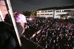 People attend a music concert to celebrate the new year in Mbare, Harare, Friday, Jan. 1, 2021. Despite a government ban on music concerts and public gatherings due to a surge in COVID-19 infections and the new and more contagious variants of the disease, thousands of people gathered in one of the country's poorest neighborhoods to celebrate the new year.(AP Photo/Tsvangirayi Mukwazhi)