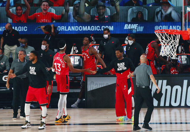 Toronto Raptors guard Kyle Lowry (7) and Toronto Raptors guard Malcolm Miller (13) celebrate after defeating the Orlando Magic in an NBA basketball game Wednesday, Aug. 5, 2020, in Lake Buena Vista, Fla. (Kim Klement/Pool Photo via AP)