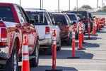 Vehicles are lined up for drive-thru COVID-19 testing in El Paso, Texas, Oct. 14, 2020. Many of those waiting for testing said they waited for over three hours to get tested at the mobile test collection site at the Socorro ISD Student Activities Complex. (Aaron E. Martinez/The El Paso Times via AP)