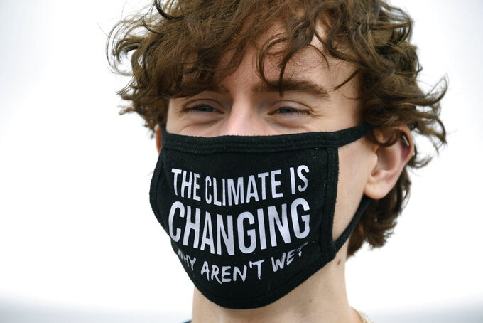 """FILE - In this Friday, June 11, 2021 file photo, a climate activist wears a protective face mask with a message which reads """"The climate is changing, why aren't we?"""" during an action on Gyllyngvase Beach in Falmouth, Cornwall, England. Britain is losing the race to adapt to the inevitable effects of climate change, including worsening heat and floods, a government-appointed panel of experts said Wednesday, June 16, 2021. The Climate Change Committee, set up to advise the government, said the level of global warming that is already inevitable would cause expensive and dangerous overheating in homes, power cuts and damage to nature, crops and food supplies. It said the government must act urgently to ensure Britain is prepared. (AP Photo/Alberto Pezzali, File)"""