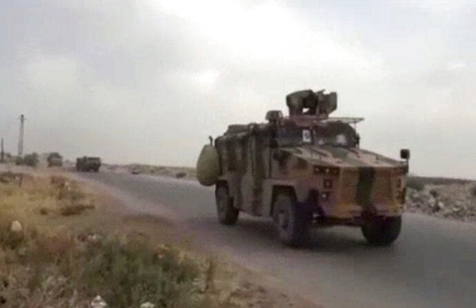 This frame grab from video provided by Central Station for Turkish Intervention, an activist-operated media group monitoring Turkish activities in Syria, that is consistent with independent AP reporting, shows a Turkish military convoy heading to some of the 12 Turkish observations points that ring Idlib, Syria, Thursday, Sept. 13, 2018. Turkey sent in military reinforcements Thursday to beef up its positions inside Syria's last rebel bastion Idlib, activists reported, even as the Turkish defense minister said Ankara is still trying with Russia and Iran to prevent a humanitarian tragedy in the case of a threatened Syrian government offensive. (Central Station for Turkish Intervention, via AP)