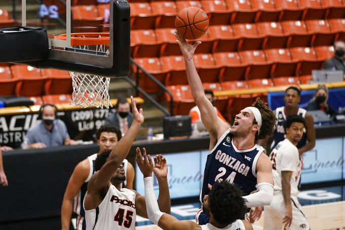 Gonzaga forward Corey Kispert (24) goes to the basket against Pacific forward Nigel Shadd (45) during the first half of an NCAA college basketball game in Stockton, Calif., Thursday, Feb. 4, 2021. (AP Photo/Rich Pedroncelli)