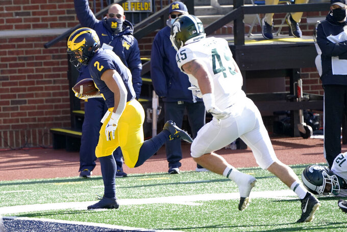 Michigan running back Blake Corum (2) beats Michigan State linebacker Noah Harvey (45) into the end zone for a touchdown during the first half of an NCAA college football game, Saturday, Oct. 31, 2020, in Ann Arbor, Mich. (AP Photo/Carlos Osorio)