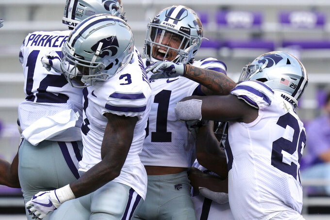 Kansas State AJ Parker (12) celebrates with teammates Kiondre Thomas (3), Jahron McPherson (31) and Khalid Duke (29) after his third-quarter interception touchdown against TCU during an NCAA college football game Saturday, Oct. 10, 2020, in Arlington, Texas. (AP Photo/Richard W. Rodriguez)