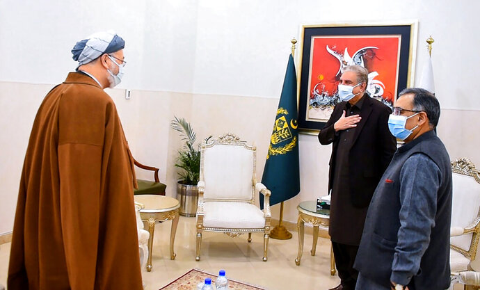 In this photo provided by Pakistan's Ministry of Foreign Affairs, Pakistani Foreign Minister Shah Mahmood Qureshi, second from right, greets Karim Khalili, left, an influential Afghan Shiite leader, upon his arrival at ministry for a meeting, in Islamabad, Pakistan, Tuesday, Jan. 12, 2021. Khalili is visiting Pakistan where members of the minority sect are still reeling from the brutal killing of 11 Shiite coal miners, nine of whom were Afghan immigrants, earlier this month. (Ministry of Foreign Ministry via AP)