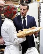 French President Emmanuel Macron speaks with a bread maker during a visit to the International Agriculture Fair (Salon de l'Agriculture) at the Porte de Versailles exhibition center in Paris, Saturday, Feb. 22, 2020. (Benoit Tessier/Pool via AP)