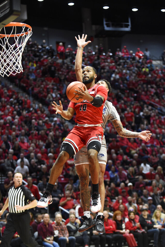 San Diego State guard KJ Feagin (10) shoots past the defense of Nevada guard Jalen Harris during the first half of an NCAA college basketball game Saturday, Jan. 18, 2020, in San Diego. (AP Photo/Denis Poroy)