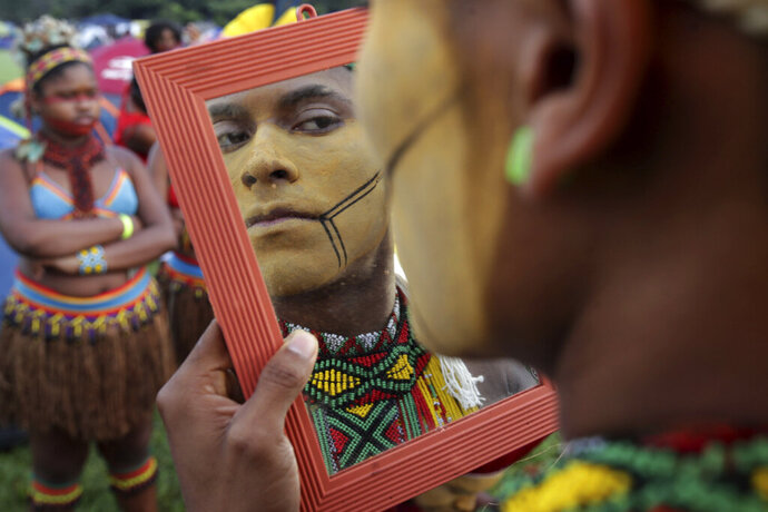 In this April 24, 2019 photo, a young indigenous man applies body paint as he checks himself out in a mirror, during an annual three-day campout protest known as the Free Land Encampment, in Brasilia, Brazil. The event begins amid animosity between Brazil's indigenous groups and the new government of far-right President Jair Bolsonaro. (AP Photo/Eraldo Peres)