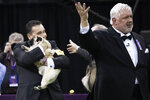 Handler Esteban Farias hugs Biggie, a pug, after he won the Toy group competition during the 142nd Westminster Kennel Club Dog Show, Monday, Feb. 12, 2018, at Madison Square Garden in New York. Biggie won best in group. (AP Photo/Mary Altaffer)