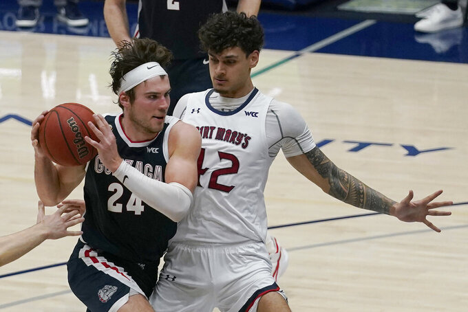 Gonzaga forward Corey Kispert (24) drives against Saint Mary's forward Dan Fotu during the second half of an NCAA college basketball game in Moraga, Calif., Saturday, Jan. 16, 2021. (AP Photo/Jeff Chiu)