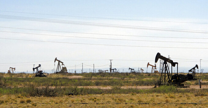 FILE - In this April 9, 2014, file photo, oil rigs stand in the Loco Hills field on U.S. Highway 82 in Eddy County near Artesia, N.M., one of the most active regions of the Permian Basin. In the closing months of the Trump administration energy companies stockpiled enough drilling permits for western public lands to keep pumping oil for years. That stands to undercut President-elect Joe Biden's plans to block new drilling on public lands to address climate change. (AP Photo/Jeri Clausing, File)