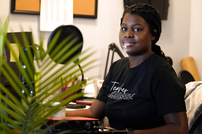 A Chicago charter school teacher Angela McByrd poses for a photo before work on her laptop to teach remotely from her home in Chicago, Thursday, Sept. 24, 2020. Most students in Illinois have been starting remote learning this fall, according to results from an Illinois State Board of Education survey. (AP Photo/Nam Y. Huh)