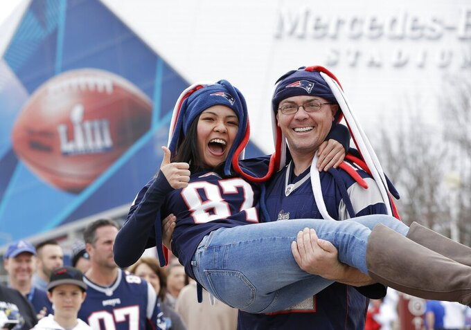 New England Patriots fans pose outside the Mercedes-Benz Stadium before the NFL Super Bowl 53 football game between the Los Angeles Rams and the New England Patriots, Sunday, Feb. 3, 2019, in Atlanta. (AP Photo/Mark Humphrey)