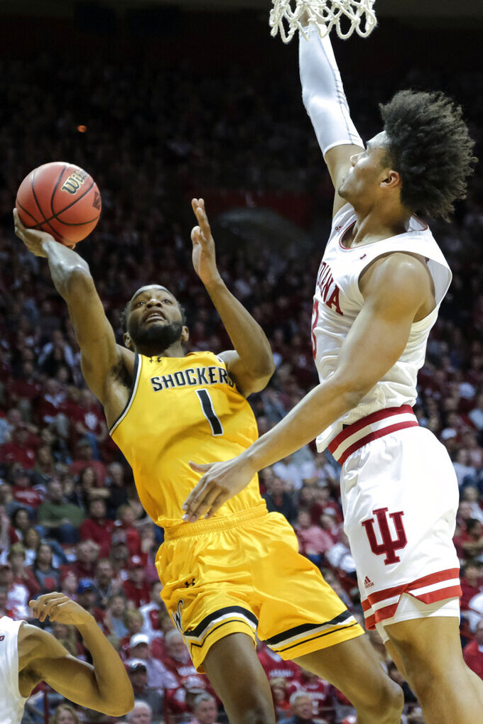 Wichita State forward Markis McDuffie (1) shoots in front of Indiana forward Justin Smith (3) in the first half of an NCAA college basketball game in the third round of the NIT tournament in Bloomington, Ind., Tuesday, March 26, 2019. (AP Photo/AJ Mast)