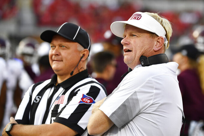 Eastern Kentucky head coach Walt Wells, right, discusses a call with a referee during the first half of an NCAA college football game against Louisville in Louisville, Ky., Saturday, Sept. 11, 2021. (AP Photo/Timothy D. Easley)