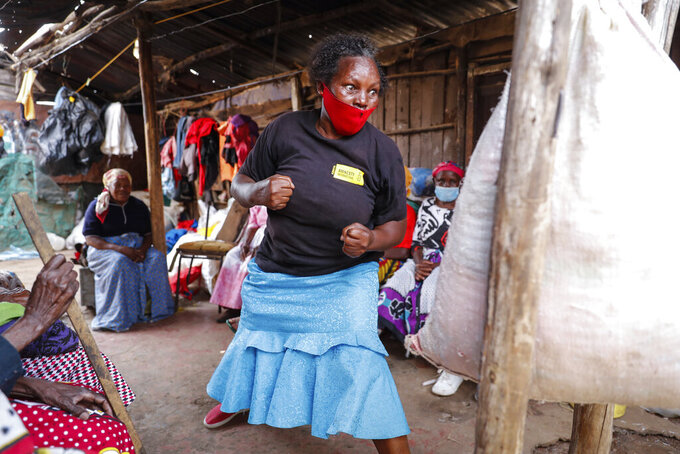 """Group leader Jane Waithageni Kimaru, 60 years old, strikes a punching bag to show women how to fight off a potential rapist and escape, during a Taekwondo self-defense class for women in the Korogocho slum of Nairobi, Kenya, Thursday, Sept. 16, 2021. In Korogocho, which means """"crowded shoulder to shoulder"""" in Swahili, the women meet every week to train in skills they hope can help them fight back if they are sexually assaulted. (AP Photo/Brian Inganga)"""