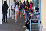 Shoppers wear protective face masks as they look for Black Friday deals at the Ellenton Premium Outlet stores Friday, Nov. 27, 2020, in Ellenton, Fla. Attendance at the mall was down in an attempt to avoid spreading the corona virus. (AP Photo/Chris O'Meara)