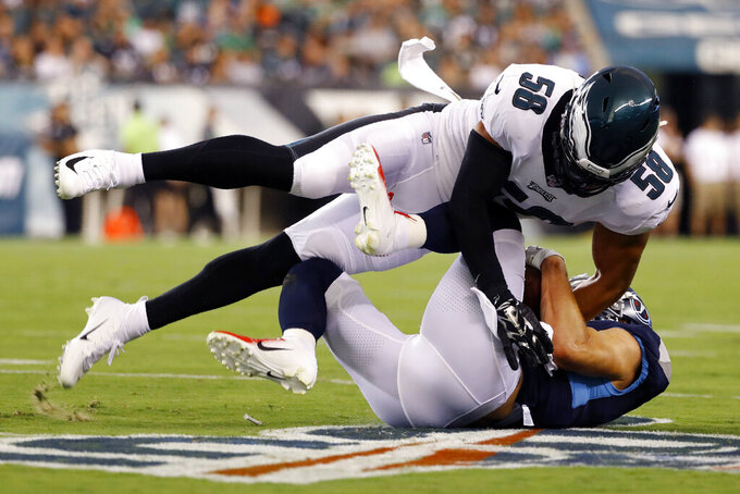 Philadelphia Eagles' L.J. Fort, top, tackles Tennessee Titans' Adam Humphries during the first half of a preseason NFL football game Thursday, Aug. 8, 2019, in Philadelphia. (AP Photo/Michael Perez)